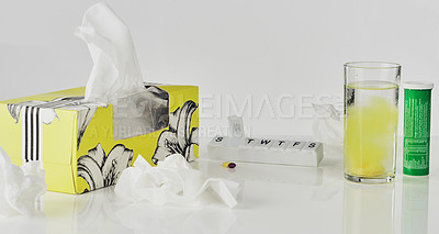 Buy stock photo Cropped shot of cold and flu medication next to a box of tissues on the tabletop of an empty kitchen