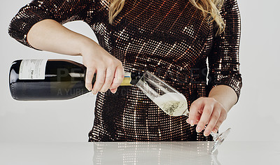 Buy stock photo Cropped shot of an unrecognizable woman standing and pouring a bottle of champagne into a glass in the studio