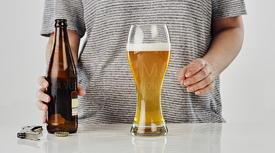 Buy stock photo Cropped shot of an unrecognizable woman standing with a bottle of beer and a glass in the studio
