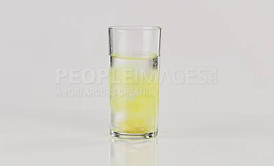 Buy stock photo Cropped shot of an effervescent fizzing in a glass of water on the tabletop of an empty kitchen