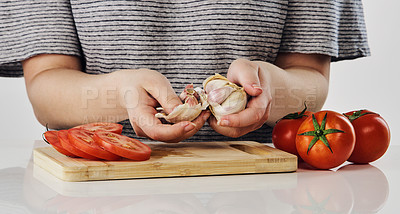 Buy stock photo Cropped shot of an unrecognizable woman breaking garlic cloves over a wooden board in the studio during the day
