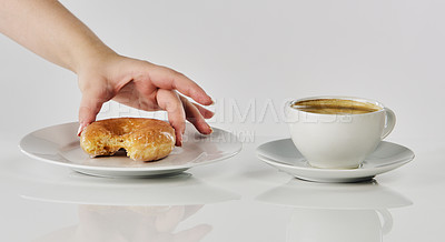 Buy stock photo Cropped shot of an unrecognizable woman putting her bitten glazed donut on a saucer next to her coffee