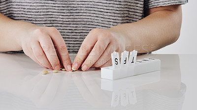 Buy stock photo Cropped shot of an unrecognizable woman organising pills into a pillbox against a gray background in the studio