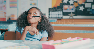 Buy stock photo Shot of a young girl looking bored while playing at a school desk