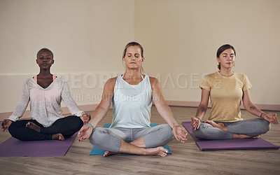Buy stock photo Full length shot of a diverse group of women sitting together and meditating after an indoor yoga session