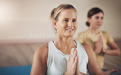 Buy stock photo Cropped shot of two young women sitting together and meditating with their palms together after an indoor yoga session