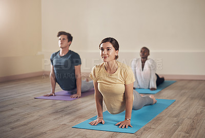 Buy stock photo Full length shot of a diverse group of yogis holding an upward facing dog during an indoor yoga session