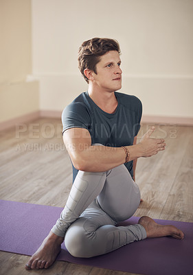 Buy stock photo Full length shot of a handsome young man sitting and holding a spinal half twist during an indoor yoga session