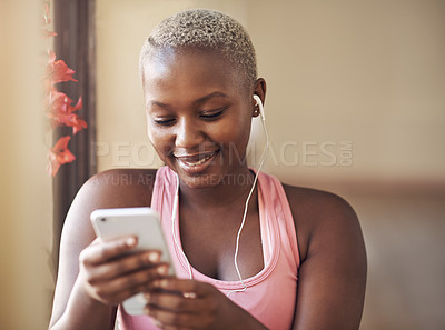 Buy stock photo Cropped shot of an attractive young woman sitting and wearing earphones while listening to music through her cellphone