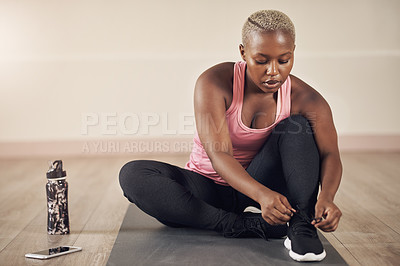 Buy stock photo Full length shot of an attractive young woman sitting alone and getting ready for a yoga session indoors