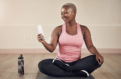 Buy stock photo Full length shot of an attractive young woman sitting alone and using her cellphone after an indoor yoga session