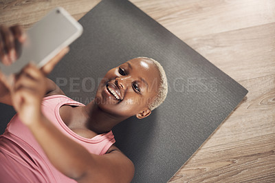 Buy stock photo Cropped shot of an attractive young woman using her cellphone to take a selfie after a yoga session indoors