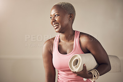 Buy stock photo Cropped shot of an attractive young woman standing alone and holding her yoga mat before an indoor yoga session