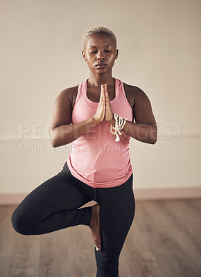 Buy stock photo Cropped shot of an attractive young woman holding a tree pose while doing yoga alone indoors