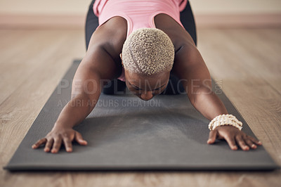 Buy stock photo Cropped shot of an unrecognizable woman holding a child's pose during an indoor yoga session alone