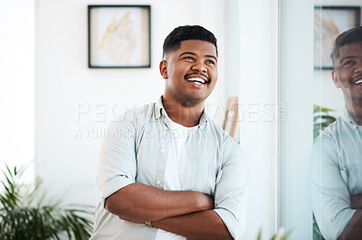 Buy stock photo Shot of a young businessman looking thoughtfully out of a window in a modern office