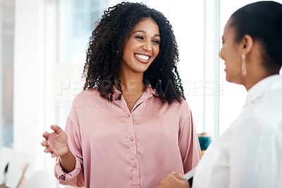 Buy stock photo Shot of two young businesswomen having a conversation in a modern office