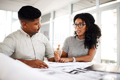 Buy stock photo Shot of a young businessman and businesswoman working on a blueprint in a modern office