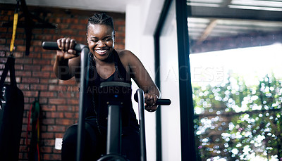 Buy stock photo Cropped shot of an attractive young female athlete working out on an elliptical machine in the gym