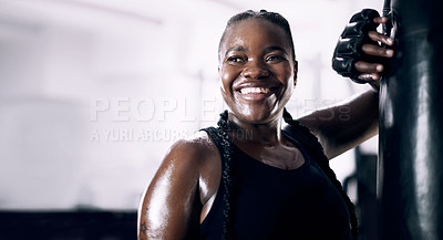 Buy stock photo Cropped shot of an attractive young female athlete leaning against a boxing bag in the gym