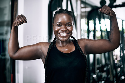 Buy stock photo Cropped portrait of an attractive young female athlete flexing her biceps while standing in the gym