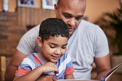 Buy stock photo Cropped shot of a cheerful young man and his son reading a storybook together at home during the day
