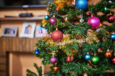 Buy stock photo Cropped shot of a Christmas tree full of decorations inside of a house during Christmas time