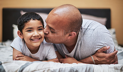 Buy stock photo Portrait of a cheerful little boy receiving a kiss on his cheek by his father while they hang out on the bed at home during the day
