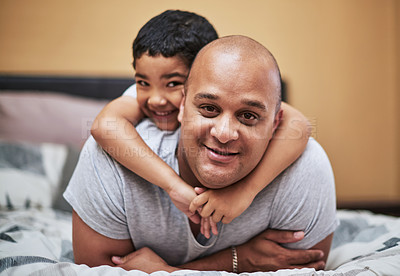 Buy stock photo Portrait of a cheerful little boy hanging on his father's back while hanging out in the bedroom at home during the day