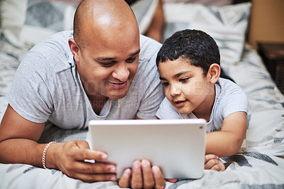 Buy stock photo Cropped shot of a cheerful young man and his son watching videos on a digital tablet together  while hanging out on a bed at home during the day
