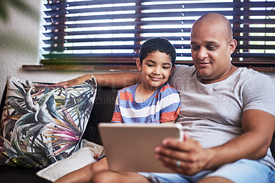 Buy stock photo Cropped shot of a cheerful young man and his son watching videos on a digital tablet together  while hanging out on a sofa at home during the day