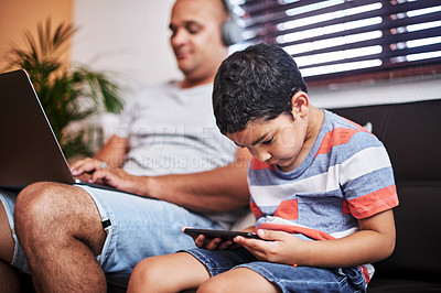 Buy stock photo Cropped shot of a carefree little boy browsing on a digital tablet while his father works on his laptop on the sofa at home during the day
