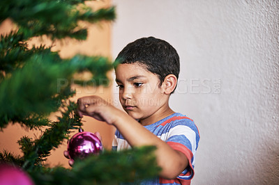 Buy stock photo Cropped shot of a carefree little boy putting up Christmas decorations on a tree at home during Christmas time