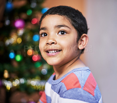 Buy stock photo Cropped shot of a cheerful little boy looking into the distance with a Christmas tree in the background at home during the day