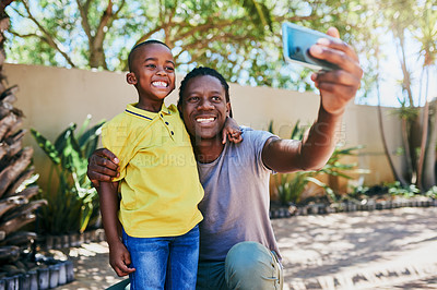 Buy stock photo Cropped shot of an affectionate young single father taking a selfie with his son in their backyard at home