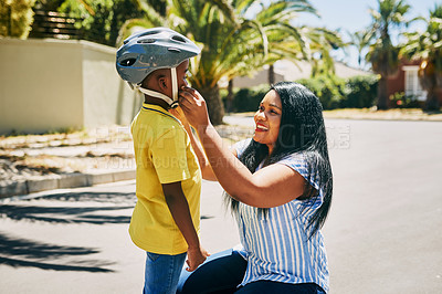 Buy stock photo Cropped shot of an affectionate young single mother adjusting her son's helmet before he rides a bike outdoors