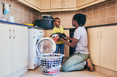 Buy stock photo Cropped shot of an adorable little boy assisting his dad with doing laundry at home
