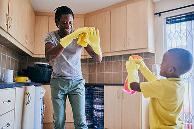 Buy stock photo Cropped shot of an affectionate young single father playing with his son while cleaning in their kitchen at home