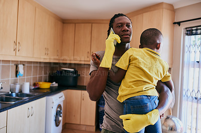 Buy stock photo Cropped shot of an affectionate young single father taking a phonecall while holding his son in the kitchen at home