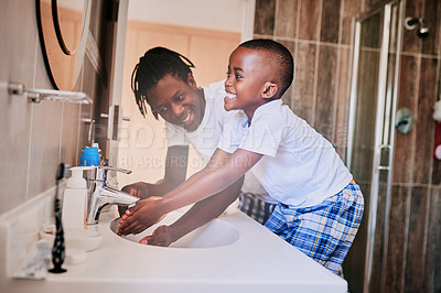 Buy stock photo Cropped shot of a man helping his son to wash his hands in the bathroom
