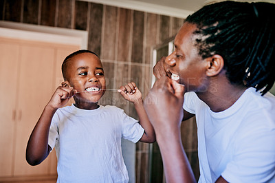 Buy stock photo Cropped shot of a young man and his son flossing their teeth in the bathroom at home