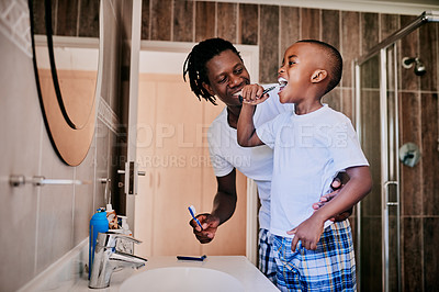 Buy stock photo Cropped shot of a young man and his son brushing their teeth in the bathroom at home