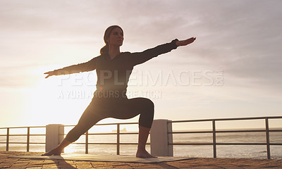 Buy stock photo Shot of a woman practising yoga on the promenade