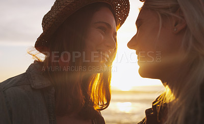 Buy stock photo Shot of an affectionate and happy young couple bonding and spending the day together outdoors near the beach