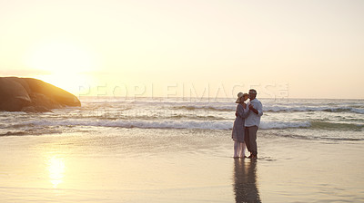 Buy stock photo Full length shot of an affectionate senior couple dancing together at the beach at sunset