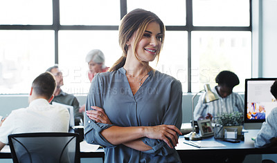 Buy stock photo Shot of a confident young businesswoman working in a modern office with her colleagues in the background
