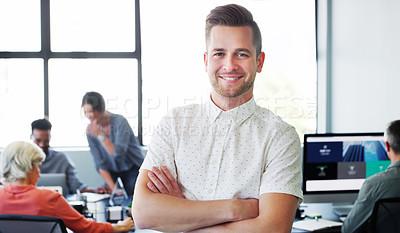 Buy stock photo Portrait of a confident young businessman working in a modern office with his colleagues in the background