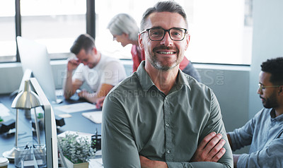 Buy stock photo Portrait of a confident mature businessman working in a modern office with his colleagues in the background
