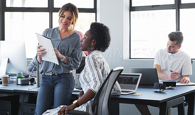 Buy stock photo Shot of two young businesswomen discussing paperwork in a modern office