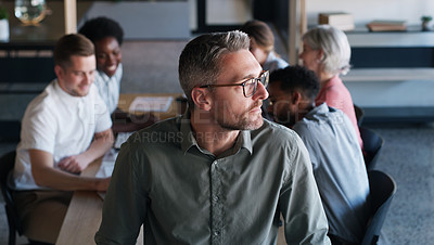Buy stock photo Shot of a confident mature businessman in in the office boardroom with his colleagues in the background